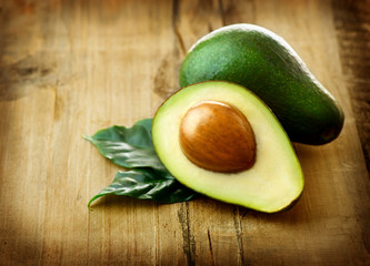 Avocado. Organic Avocados with leaves on a wooden table