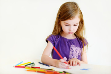 Cute girl drawing a picture with colorful pencils