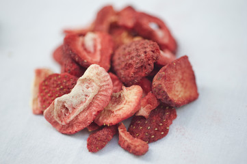 Freeze dired strawberries on a white background on a sunny day.