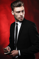 Handsome young man in suit on dark background with money