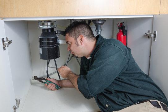 Plumber fixing a garbage disposal