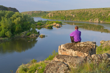 Man sits on a rock above the river