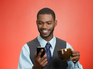 Smiling businessman reading news on mobile drinking coffee