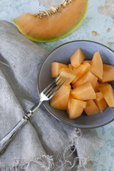 pieces of melon on bowl and slices on vintage scraped background