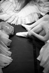 Ballerinas in puffy skirts sitting on the floor, monochrome