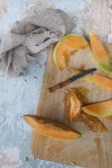 fresh melon slices with seed on chopping board