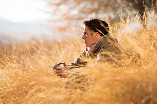 man sitting in tall grass in autumn
