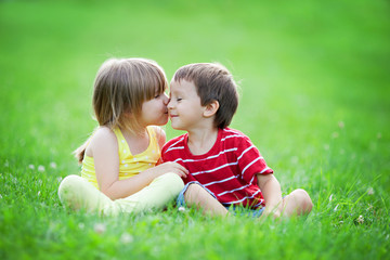Adorable boy and girl, sitting in the park, smiling and having f