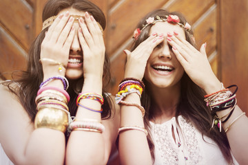 Boho girls covering eyes by hands
