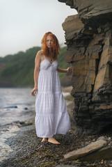 Beautiful young woman goes along the coast.