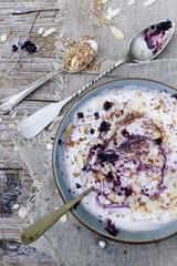 white yogurt with blackberries muesli and almond slices on bowl