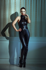 Womam in catsuit posing at vintage wall