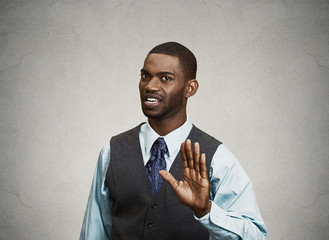 Angry executive gesturing with hands to stop, grey background