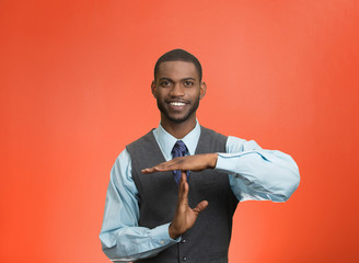 Executive man giving time out hand gesture, red background