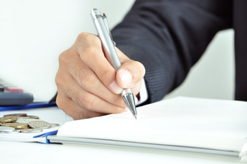 Businessman hand holding a pen writing on the book