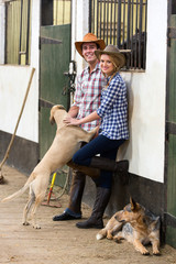 young horse farming couple in stables