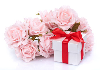 pink flowers and  gift box with red ribbon and bow on a white ba