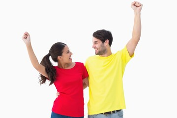 Excited couple cheering in red and yellow tshirts