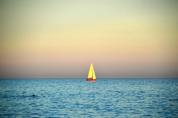 isolated sailing boat at sunset photo