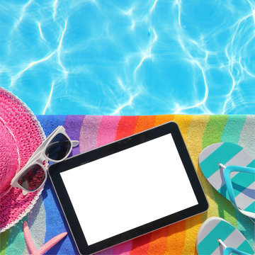 Tablet with blank screen by poolside with beach accessories