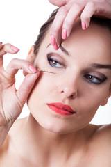 Woman using false eyelashes