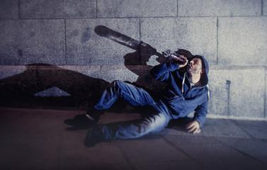 alcoholic drunk man drinking on ground street corner