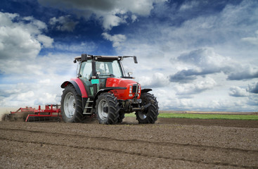 Wall Mural - Preparing land for sowing at spring, farmer in tractor