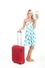 beautiful girl standing with luggage and smiling.