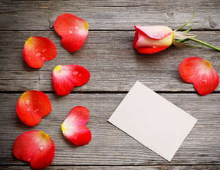 red petal with paper on wooden background