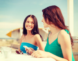 girls looking at smartphone in cafe on the beach