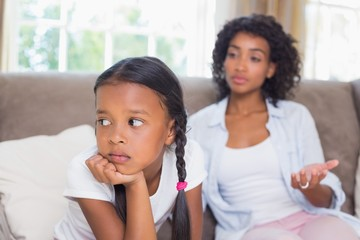 Pretty mother sitting on couch after an argument with daughter