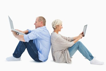 Mature couple using laptop and tablet pc