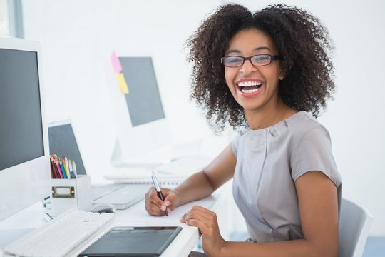Young pretty african american designer smiling at camera at her desk