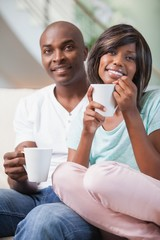 Happy couple sitting on couch having coffee