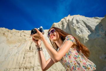 Woman traveler taking photo on the sandy background