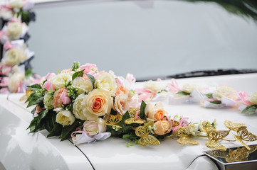 Wedding car decoration of flowers with roses and butterflies