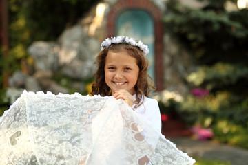 Obraz Dziewczynka, uśmiechnięta z wianuszkiem na głowie. - fototapety do salonu