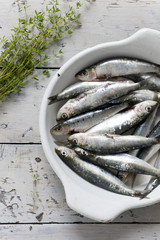 sardines on enamelled tray with thyme on rustic background