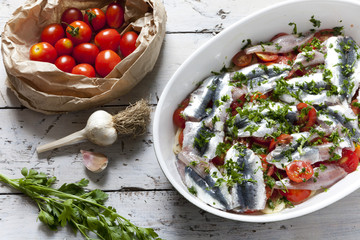 fresh raw sardines on casserole with cherry tomatoes slices
