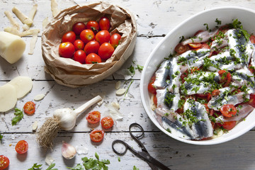 sardines on tray with cherry tomatoes slices and parsley