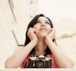 closeup of beautiful young woman holding a vintage camera