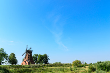 old brick windmill on field on blue sky background