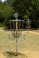 Two disc golf baskets in a park