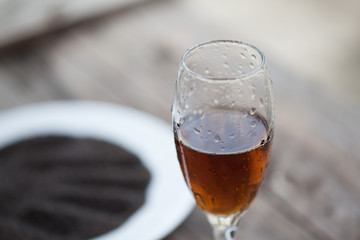 Glass of cognac with Dry sweet basil seed standing on a wooden t