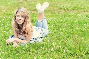 happy young beautiful sexy girl lying on the grass and smiles