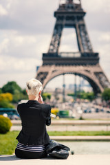 Young woman taking a photo with mobile phone in Paris, France.