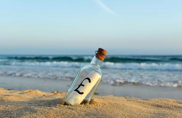 British pound in a bottle on the beach