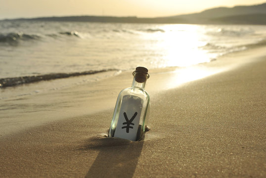 Yen, currency of Japan in a bottle on the beach, rising sun