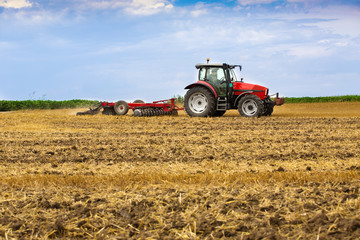Wall Mural - Tractor cultivating wheat stubble field, crop residue.