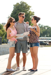 smiling friends with map and city guide outdoors